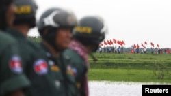FILE - Cambodian police officers stand guard as Vietnamese people wave their national flags at the Cambodia-Vietnam border in Svay Rieng province, July 19, 2015.