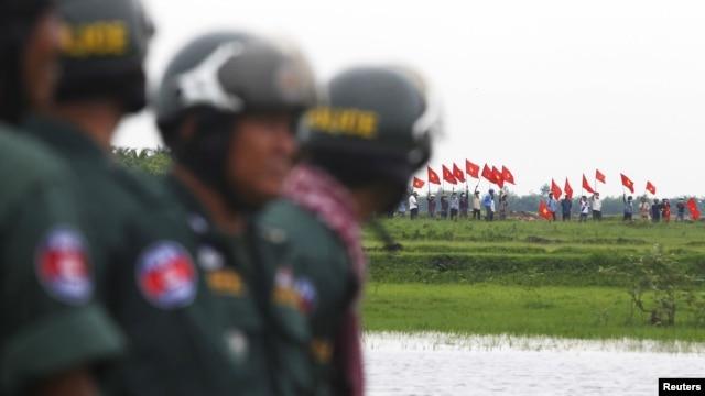 Cảnh sát Campuchia đứng canh gác trong lúc người Việt phất cờ từ bên kia biên giới giữa hai nước.