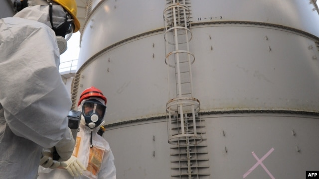 Japanese Economy, Trade and Industry Minister Toshimitsu Motegi (R) in a radiation protection suit inspects a contaminated water tank, found to be have a huge leak of radioactive water, August 26, 2013.