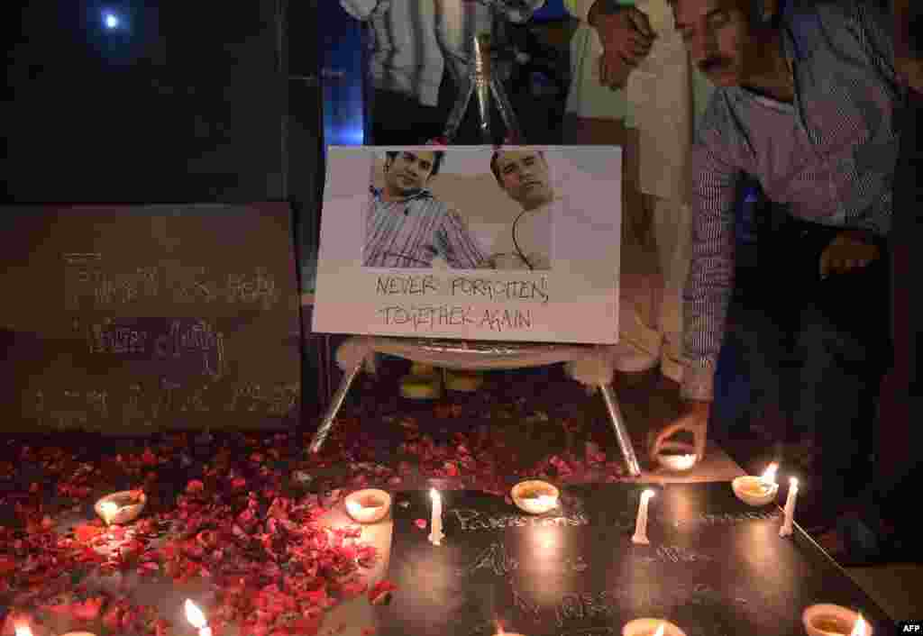 Pakistani journalists light candles and oil lamps next to a photograph of Agence France-Presse (AFP) chief photographer for Afghanistan Shah Marai, who was killed along with other Afghan journalists in a targeted suicide bombing, during a vigil in Islamabad.