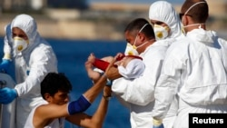 Seorang pria mengulurkan bayinya yang sakit kepada tentara Malta setelah diselamatkan di pelabuhan Valletta, Malta (28/8). (Reuters/Darrin Zammit Lupi)