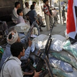 Tribal fighters backing protesters sit on alert behind sandbags during a demonstration to demand the trial of Yemen's outgoing President Ali Abdullah Saleh in the southern city of Taiz, December 5, 2011