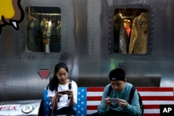 FILE - Shoppers sit on a bench with a decorated with U.S. flag browsing their smartphones outside a fashion boutique selling U.S. brand clothing at the capital city's popular shopping mall in Beijing, Sept. 24, 2018.