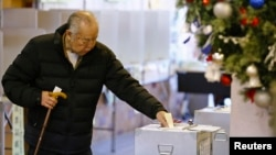 A man casts his ballot in a lower-house parliamentary election in Tokyo, Dec. 14, 2014.