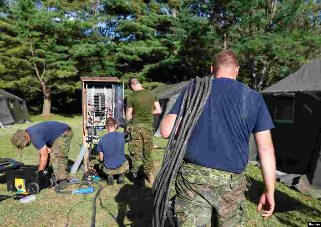Members of the Canadian Armed Forces install electricity for the tents erected to house asylum seekers at the Canada-U.S. border in Lacolle, Quebec, Aug. 9, 2017.