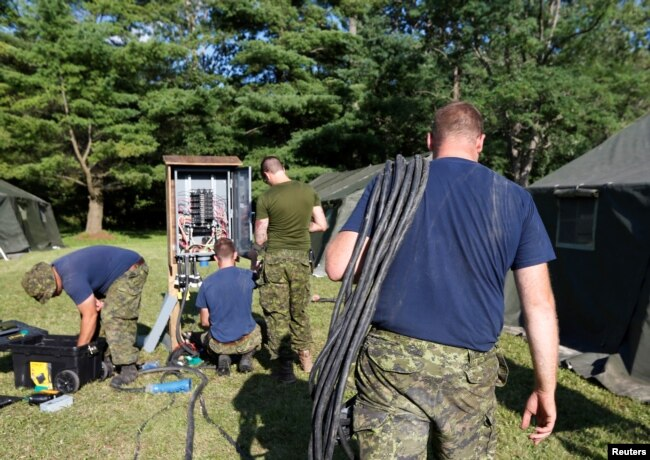 Members of the Canadian Armed Forces install electricity for the tents erected to house asylum-seekers at the Canada-U.S. border in Lacolle, Quebec, Aug. 9, 2017.
