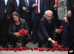 Kemal Kilicdaroglu, right, head of Republican People's Party, Turkey's main opposition party, accompanied by his wife Selvi, lay flowers at the site of Saturday's bombing attacks in Ankara, Oct. 11, 2015.