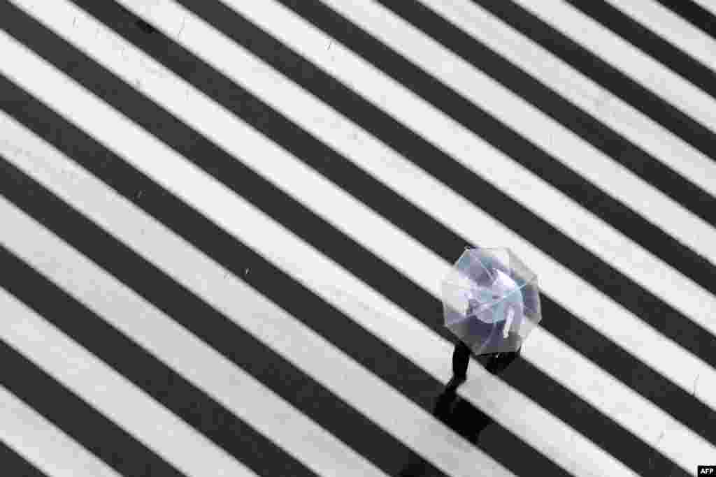 A pedestrian crosses a street on a rainy day in Tokyo.