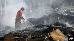 1月6号,泰国遭受50年来最严重的水灾已经退去,一名消防员正在扑灭废墟上的火。