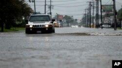 Une voiture conduit dans une rue inondée au Lac Charles, le 27 août 2017.