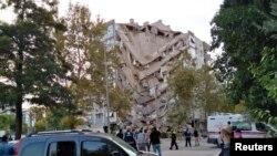 Egey dənizində baş verən güclü zəlzələdən sonra İzmirdə yerli sakinlər zədələnmiş bir binaya baxırlar. 30 oktyabr, 2020. REUTERS/Tuncay Dersinlioglu