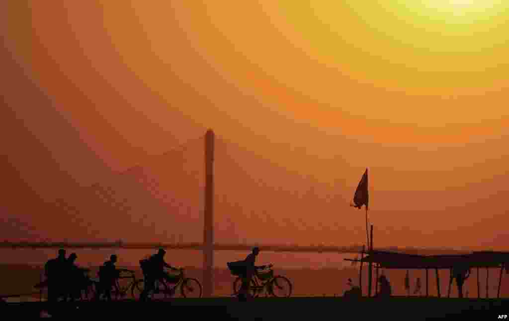 Indian priests cycle home at Sangam, the confluence of the rivers Ganges, Yamuna and the mythical Saraswati in Allahabad.