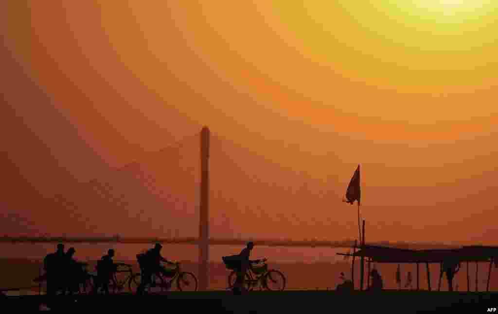 موبدان هندی در سنگام با دوچرخه به خانه می روند. سنگام در محل تلاقی رودخانه های گنگ و يامونا در الله آباد است.