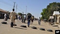 Vigilantes barricade a road after twin blasts exploded at a crowded market in Maiduguri, Nigeria, Dec. 1, 2014.