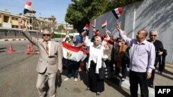 Les Egyptiens dansent avec des drapeaux égyptiens devant un bureau de vote au Caire, le 26 mars 2018.