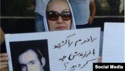خانم راحمی پور در پلاکاردی به عدم پاسخ حکومت به کشتن برادرش معترض است.