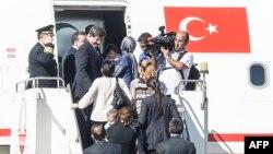 Thủ tướng Thổ Nhĩ Kỳ Ahmet Davutoglu (trái) vào máy bay với các con tin ngày 20/9/2014, tại sân bay ở thành phố Sanliurfa, miền nam Thổ Nhĩ Kỳ, gần biên giới Syria.