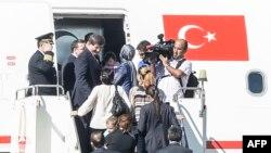 터키의 다부토울루 총리가 20일 터키 남부 산리우르파의 공항에서 ISIL에 억류됐던 인질들과 함께 비행기에 오르고 있다.
