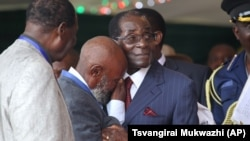 FILE An unidentified man who was in jail with Zimbabwean President Robert Mugabe during the liberation struggle, cries, as he greets him, during celebrations to mark his 92nd Birthday celebrations in Masvingo about 300 kilometres south of Harare, Saturday, Feb, 27, 2016. (AP Photo/Tsvangirayi Mukwazhi)
