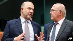 France's Finance Minister Michel Sapin, right, talks with European Commissioner for Economic and Financial Affairs Pierre Moscovici during an Eurogroup finance ministers meeting at the EU Council building in Brussels, Dec. 7, 2015.