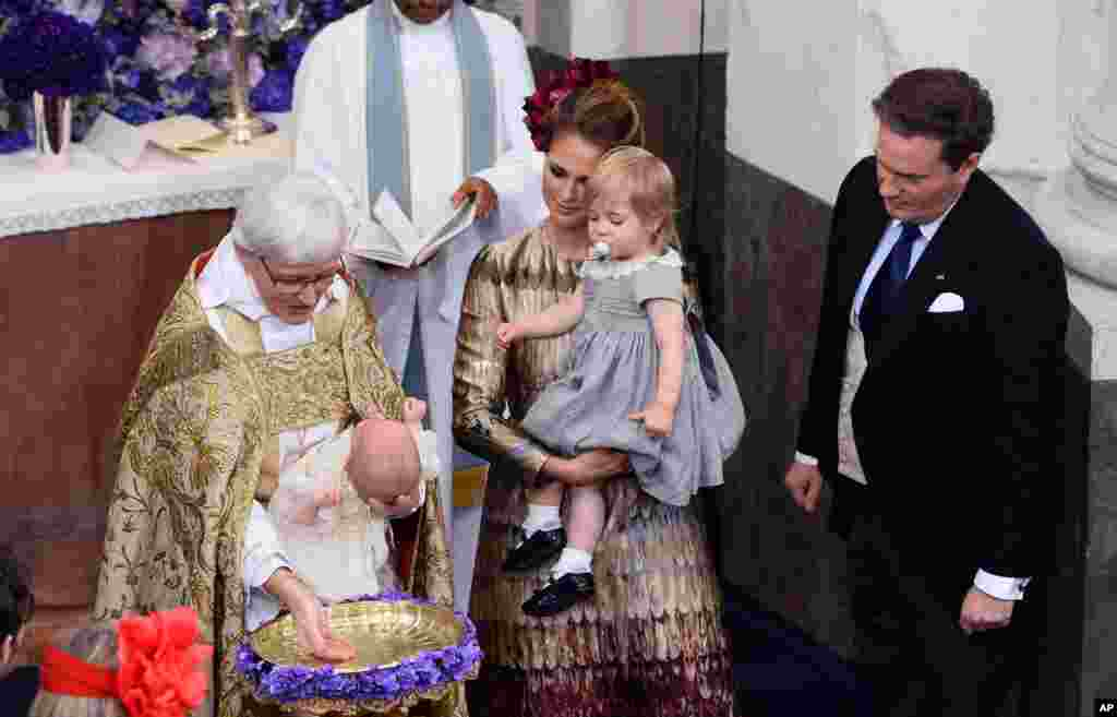 Arch Bishop Antje Jackelen baptizes Sweden's Prince Nicolas, watched by Princess Madeleine holding Princess Leonore, center, and Christopher O'Neill, during a ceremony, at the Drottningholm Palace Church, near Stockholm.