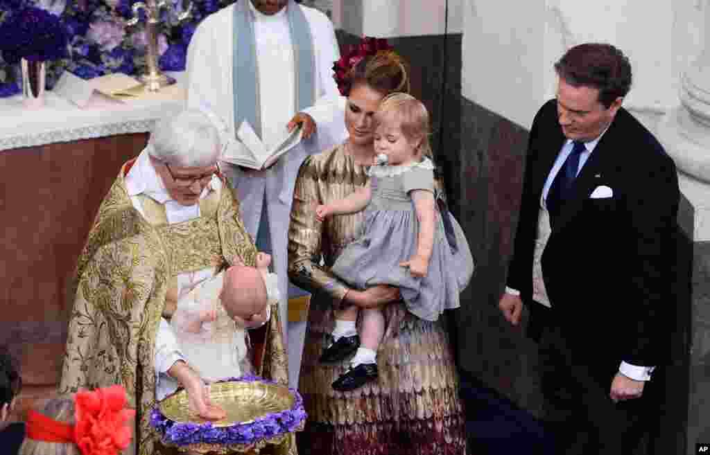 លោក Arch Bishop Antje Jackelen ធ្វើពិធីជ្រមុជទឹកឲ្យព្រះរាជបុត្រ Nicolas របស់ស៊ុយអែត (Sweden) ដែលទតដោយព្រះនាង Madeleine ដែលកំពុងពរព្រះនាង Leonore (រូបកណ្តាល) និងព្រះស្វាមី Christopher O'Neill ក្នុងពេលធ្វើពិធីនៅព្រះវិហារ Drottningholm Palace នៅក្បែរក្រុងស្តុបខុល (Stockholm) ប្រទេសស៊ុយអែត។