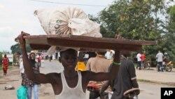 Un jeune homme porte ses affaires sur sa tête à Bujumbura, capitale du Burundi, le 7 novembre 2015. (AP Photo)