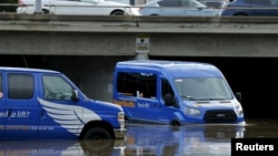 A driver moves his airport shuttles van through flood waters following an El Nino-strengthened storm in San Diego, California, Jan. 6, 2016.