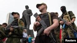 Pasukan separatis pro-Rusia bersenjata di depan monumen Vladimir Lenin di Donetsk, Ukraina timur (21/6).