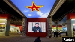 A visitor watches a video showing Chinese President Xi Jinping at a military meeting during an exhibition displaying China's achievements for the past five years, as a part of the celebrations of the upcoming 19th National Congress of the Communist Party of China.