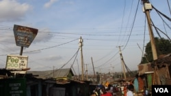 Wires are seen interwoven above the houses, connecting house to house in Kibera, Kenya. The maze of wires makes it difficult to tell the legal connections from the illegal ones. (R. Ombuor/VOA)