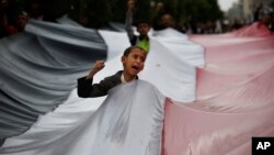 Mvulana akipiga kelele akiwa amejipenyeza kwenye bendera ya waasi wa Kihouthi wakati wa maandamano dhidi ya shambulizi la anga lililofanywa na Saudia Arabia nchini Yemen.