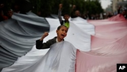 FILE - A boy chants slogans through a gap in a national flag raised by Shi'ite rebels, known as Houthis, during a protest against Saudi-led airstrikes in Sanaa, Yemen, April 15, 2016.