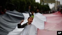 Un petit garçon portant le drapeau des rebelles shiites Houthis a Sanaa, le 15 avril 2015.