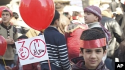 "A young boy holds up a sign that reads, ""Hama 1982,"" during a protest against Syria's President Bashar al-Assad after Friday prayers in Idlib February 3, 2012."
