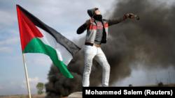 Un manifestante palestino lanza piedras contra tropas israelíes cerca de la frontera de la Ciudad de Gaza. 15 diciembre 2017. REUTERS/Mohammed Salem.
