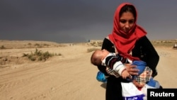 19일 이라크 군의 모술 탈환작전이 계속된 가운데, 주변 카이야라 마을의 한 여성이 아기를 안고 피난길에 올랐다.