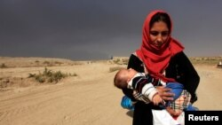 A displaced woman who is fleeing from clashes holds her baby in Qayyarah, during an operation to attack Islamic State militants in Mosul, Iraq, Oct. 19, 2016.