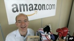 Jeff Bezos, fondateur d'Amazon, poste avec le premier livre vendu en ligne par le site Internet à Seattle, Washington, le 17 juin 2005