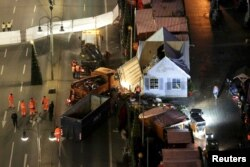 Workers clear the site of the Christmas market in Berlin, Germany, Dec. 21, 2016, after a truck plowed through a crowd at the Christmas market Monday night.