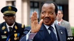 FILE - Cameroon's president, Paul Biya, waves as he arrives at an EU-Africa summit on April 3, 2014, at EU Headquarters in Brussels. In a rare public appearance, Biya on Friday paid homage to four top military officers killed in a helicopter crash last month and urged fellow citizens to unite in the fight against Boko Haram.