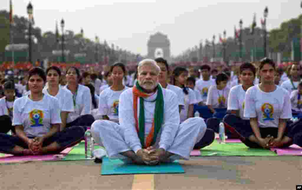 Indian Prime Minister Narendra Modi, center, sits on a mat as he performs yoga along with thousands of Indians on Rajpath, in New Delhi, India, Sunday, June 21, 2015. Millions of yoga enthusiasts are bending their bodies in complex postures across India