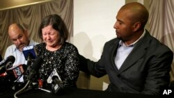 Former NFL player Dorsey Levens, right, extends a hand as Mary Ann Easterling, the widow of former NFL player Ray Easterling, reacts during a news conference, April 9, 2013, in Philadelphia, after a hearing to determine whether the NFL faces years of litigation over concussion-related brain injuries.