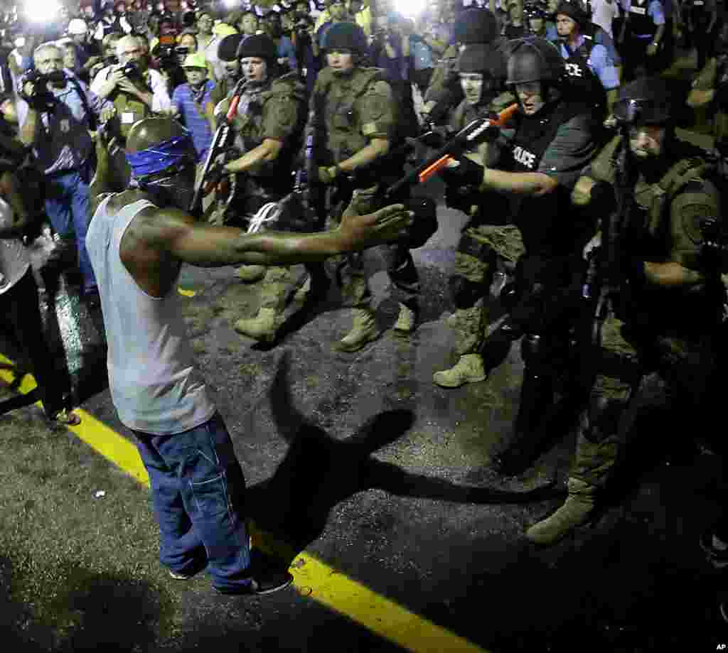 Police arrest a man as they break up a crowd of protesters, in Ferguson, Missouri, Aug. 20, 2014.