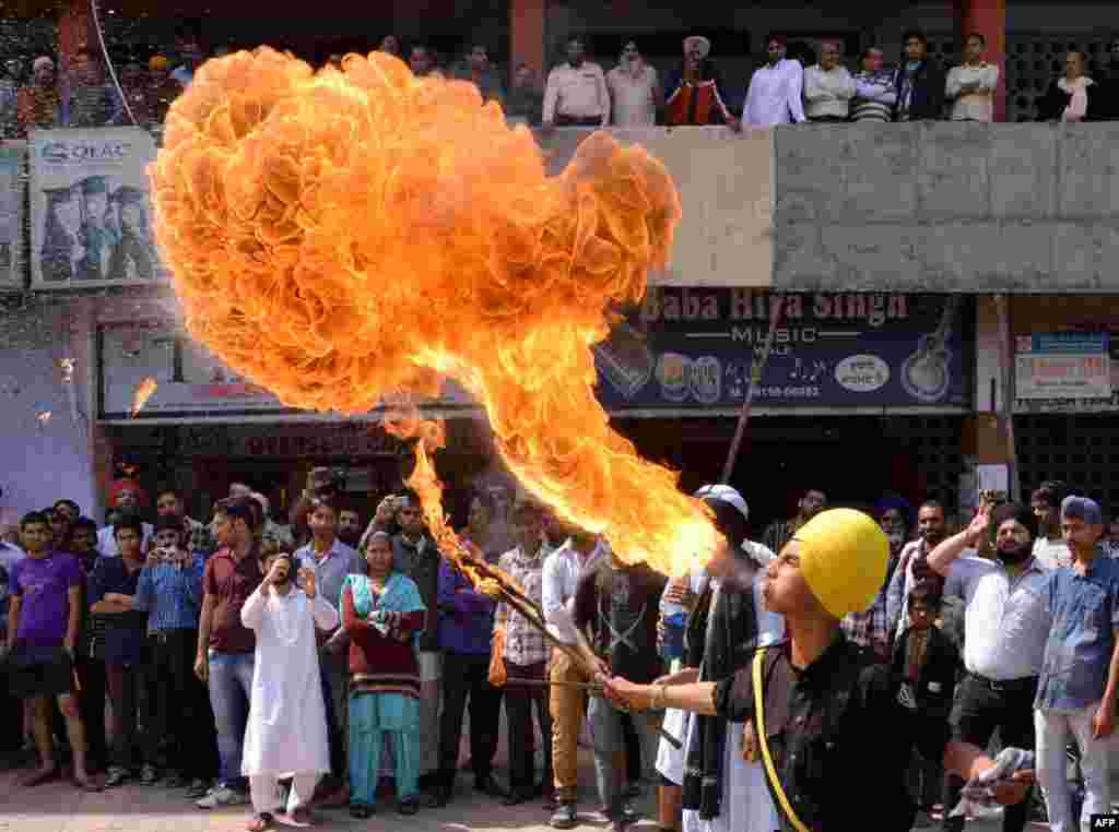 Indian Sikh youths perform fire-breathing as they demonstrate Gatka martial arts skills while welcoming unseen Bharatiya Janata Party (BJP) senior leader and candidate for Amritsar's parliamentary seat Arun Jaitley to an event in Amritsar.