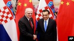 2015年11月26日,第四次中国-中东欧国家领导人会晤,李克强(右)同克罗地亚议长莱科举行会谈时握手。