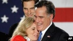 前麻薩諸塞州州長羅姆尼星期二晚在在愛奧華州德梅因舉行共和黨基層會議的晚會上和他的太太擁抱。