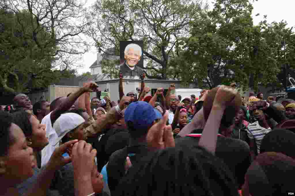 Crowds sing and chant outside Mandela's Houghton home in South Africa. (Hannah McNeish for VOA)