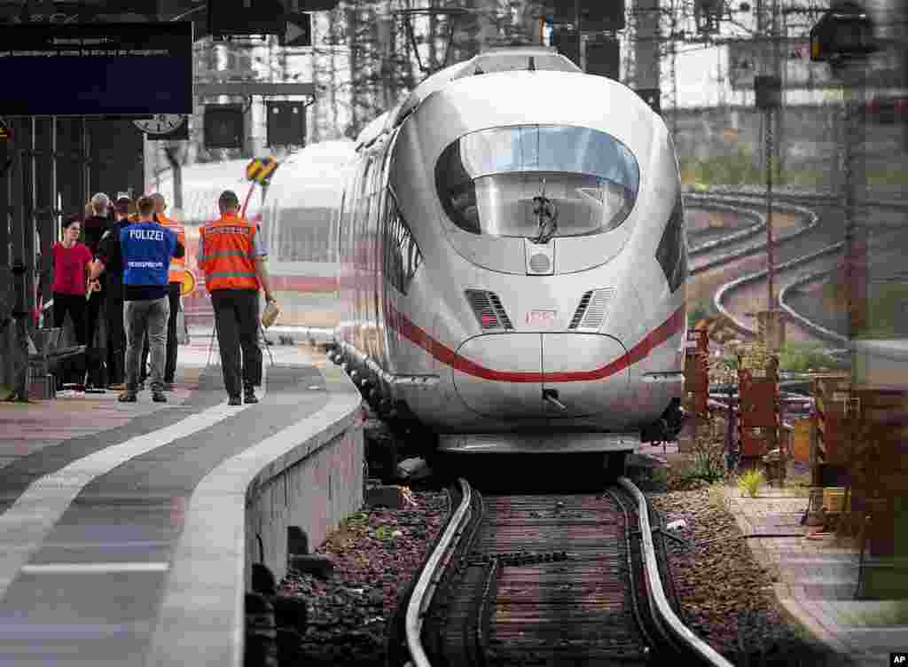 A police officer walks next to an ICE highspeed train at the main station in Frankfurt, Germany. An 8-year-old boy was run over by the train and killed at Frankfurt's main station after a man pushed him and his mother onto the tracks. The mother was able to escape but the boy suffered fatal injuries.