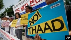 South Korean protesters hold signs during a rally to denounce deploying the Terminal High-Altitude Area Defense, or THAAD, in front of Defense Ministry in Seoul, South Korea, July 8, 2016.